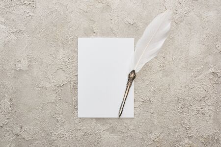 top view of quill pen on white empty card on grey textured surface