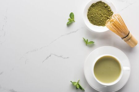 top view of green matcha tea with mint on white table