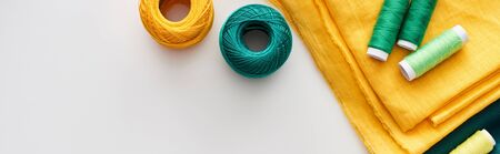 panoramic shot of fabric, knitting yarn balls and threads on white background