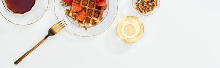 panoramic shot of bowls with nuts and honey near tea and plate with waffles on white
