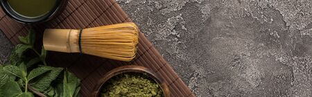 top view of traditional matcha green tea on bamboo mat on dark stone table