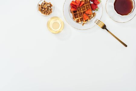 top view of bowls with nuts and honey near tea and plate with waffles on white Stockfoto