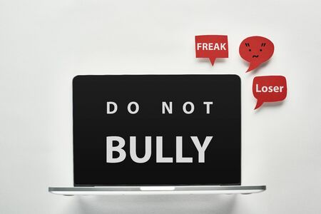 laptop with do not bully lettering on screen on white background near red speech bubbles with offensive words, cyberbullying concept