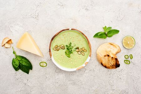 top view of tasty green creamy soup with croutons, cheese and spinach on textured grey background
