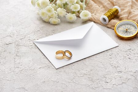 wedding rings on white envelope near chrysanthemums, beige sackcloth, spool and golden compass on textured surface Stock Photo