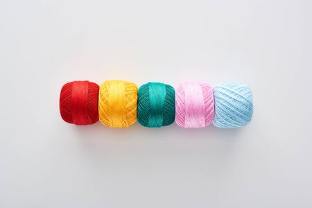 top view of bright and colorful knitting yarn balls on white background