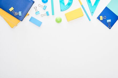 Top view of blue and yellow scattered school supplies with notepads isolated on white
