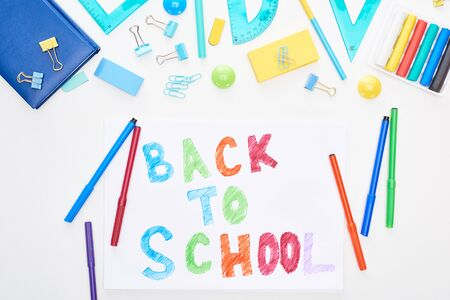 Top view of paper with back to school lettering near colorful felt-tip pens and stationery isolated on white 스톡 콘텐츠