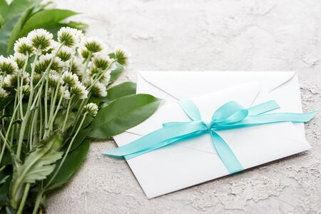 white envelopes with blue ribbon near chrysanthemums on grey textured surface