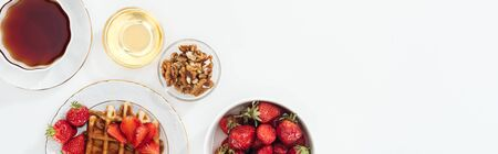 panoramic shot of breakfast with strawberries and waffle on white