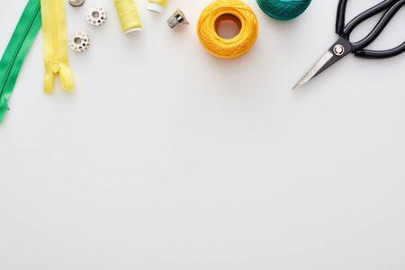 Draufsicht auf Schere, Strickgarnkugeln, Reißverschlüsse, Fäden, Fingerhut und Spulen auf weißem Hintergrund