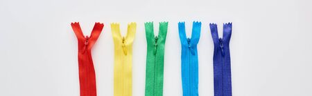 panoramic shot of bright and colorful zippers on white background