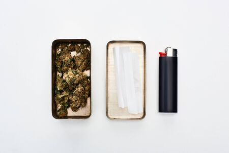flat lay with metal box with marijuana buds and rolling paper near lighter