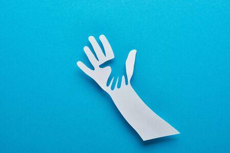 Draufsicht auf Papier geschnittene Eltern- und Kinderhände auf blauem Hintergrund