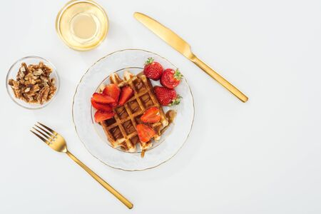 flat lay with waffles and strawberries on plate near bowls on white