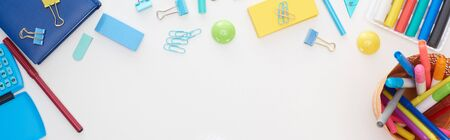 Panoramic shot of blue and yellow scattered school supplies and cup with colorful felt-tip pens isolated on white