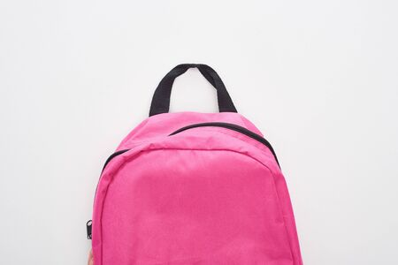 Closed bright pink school bag isolated on white