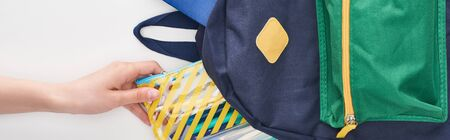Schoolgirl taking yellow pencil case from blue schoolbag isolated on white
