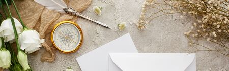 panoramic shot of quill pen on beige sackcloth near white envelope, golden compass and white flowers on grey textured surface