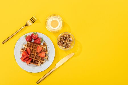 top view of served breakfast with waffles, berries, honey and nuts near cutlery on yellow Stockfoto