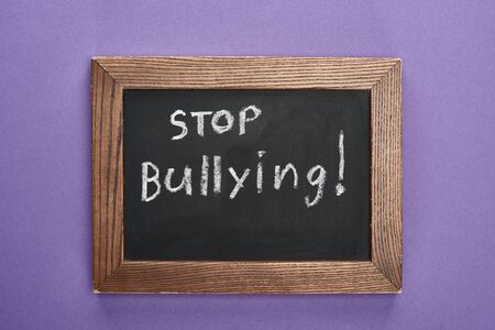 top view of chalkboard in wooden frame with stop bullying lettering on purple background Imagens