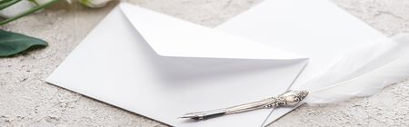panoramic shot of envelopes and quill pen on grey textured surface 版權商用圖片