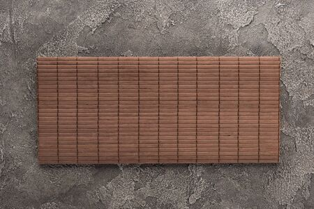 top view of bamboo mat on dark stone table