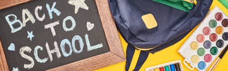 Panoramic shot of chalkboard in wooden frame with back to school inscription near blue schoolbag and watercolor paints set on yellow background
