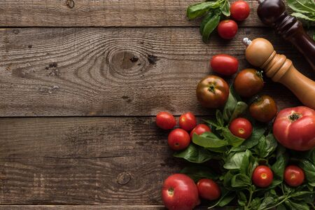 Draufsicht auf Tomaten, Spinat, Pfeffermühle und Salzmühle auf Holztisch Standard-Bild