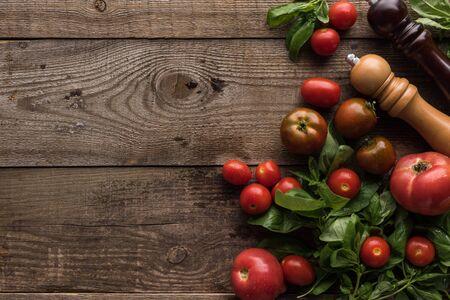 Vista superior de tomates, espinacas, molinillo de pimienta y molinillo de sal en la mesa de madera Foto de archivo