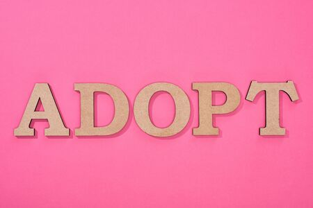 top view of cardboard word adopt on pink background
