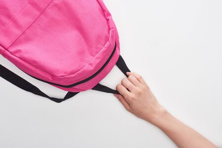 Schoolgirl holding bright pink schoolbag isolated on white