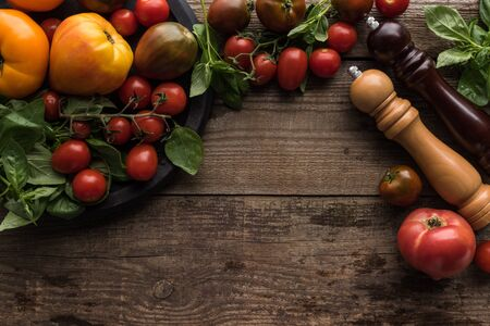 top view of pepper mill and salt mill near tomatoes and spinach on pizza pan on wooden surface Stockfoto
