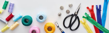 panoramic shot of zippers, scissors, thimbles, threads, knitting yarn balls, bobbins, tracing wheel on white background Фото со стока