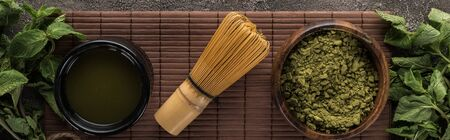 top view of green matcha tea powder with mint and whisk on bamboo mat on dark stone table