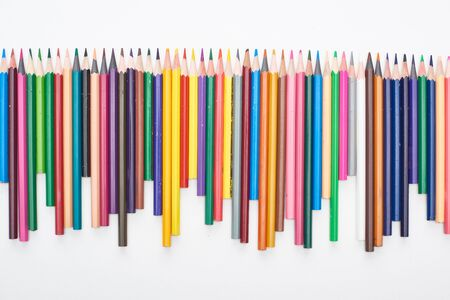 Line of different sizes color pencils isolated on white