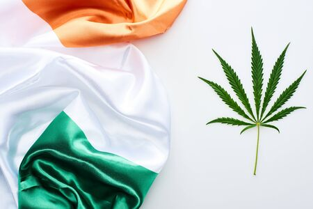 top view of green cannabis leaf near flag of Ireland on white background