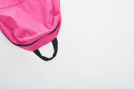 Top view of bright pink school bag isolated on white