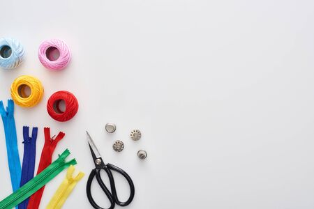 top view of zippers, scissors, thimbles, knitting yarn balls, bobbins on white background