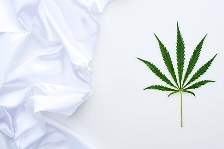 top view of green cannabis leaf near white flag on white background Stock Photo
