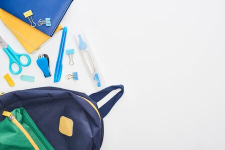 Blue schoolbag near notepads, scissors and different school supplies isolated on white Stock Photo
