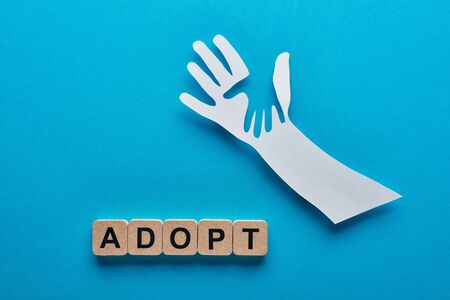 top view of paper cut parent and child hands near wooden cubes with adopt lettering on blue background