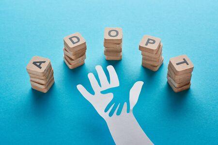 Holzklötze mit Schriftzug adoptieren in der Nähe von Papierschnitt Eltern- und Kinderhände auf blauem Hintergrund