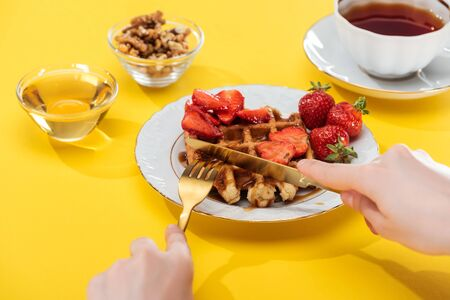 cropped view of woman cutting waffles on plate near bowl and cup with tea on yellow background