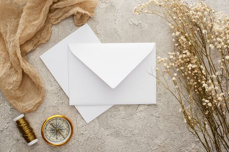 top view of white envelope and card near flowers, beige sackcloth and golden compass on textured surface Stock Photo