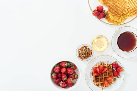 top view of tasty breakfast with strawberries and waffles on white Stockfoto