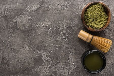top view of matcha green tea and whisk on dark stone table