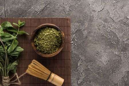 top view of green matcha tea with mint and whisk on bamboo mat on dark stone table Reklamní fotografie