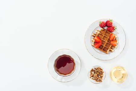 top view of waffle with strawberries on plate near cup with tea, bowls with honey and nuts on white Stockfoto