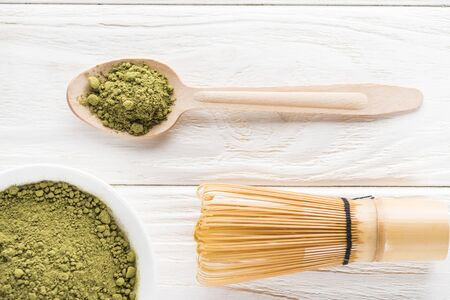 top view of wooden spoon with powder of green matcha tea and whisk
